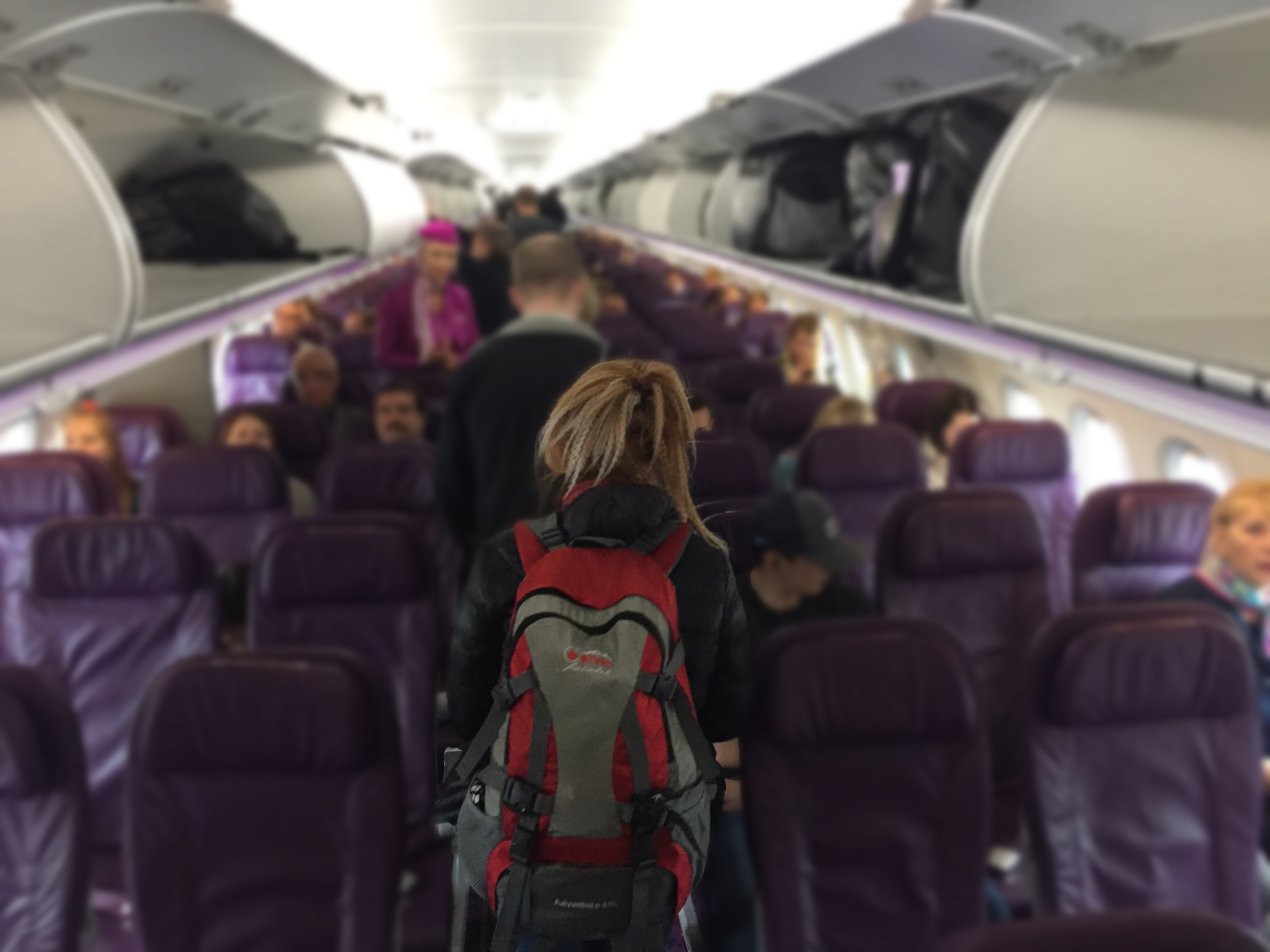person walking down aisle in an airplane